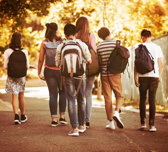 Kids wearing backpacks walking in the street.