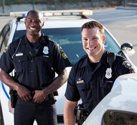 Police officers smiling next to police car.