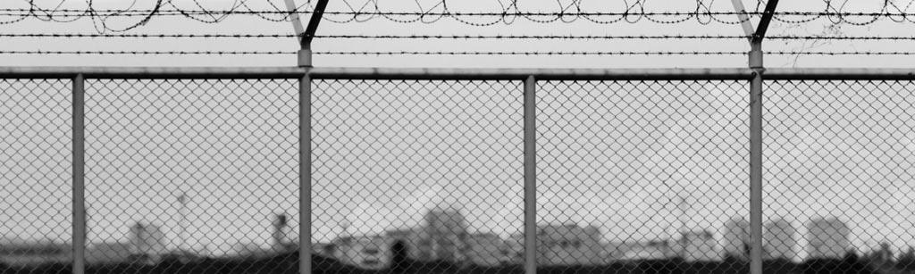 image of chain link fence topped with barbed wire